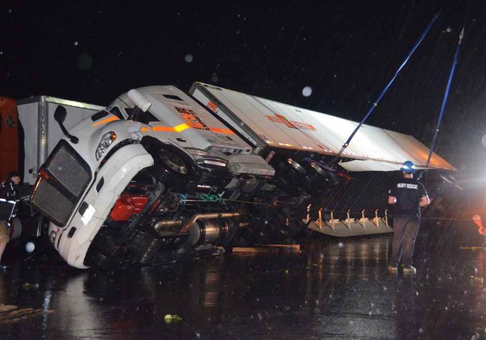 VIRGINIA ANNABLE   NEWS-TOPIC  Keen Towing crews turn a tractor-trailer back on its wheels after it was toppled over by tornado winds Sunday evening in the parking lot behind Burger King near the intersection of U.S. 321 and Mount Herman Road.